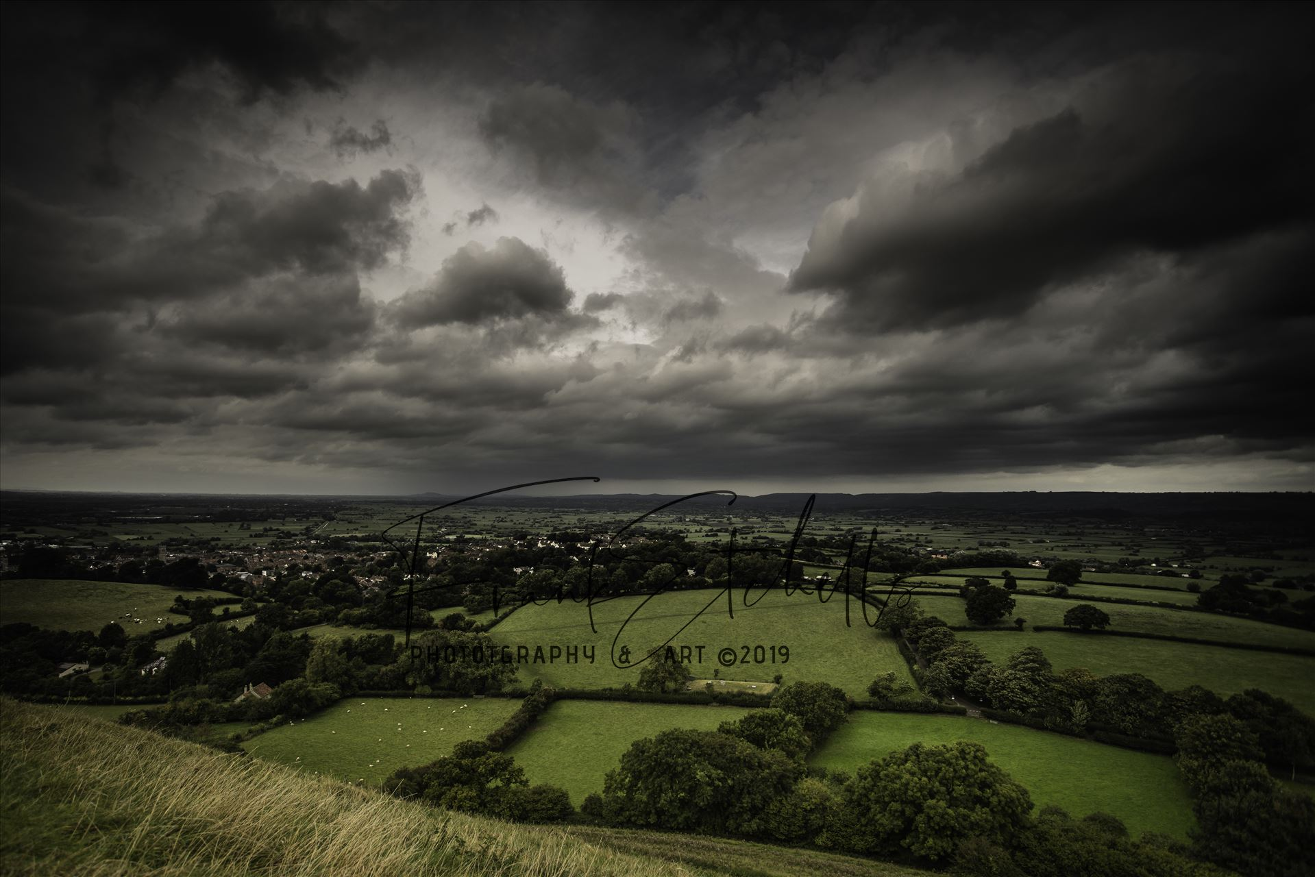 Approaching Storm Clouds - The wind blew strongly at the top and towards St. Michael's tower overlooking the surrounding lands bringing the clouds with it, they darkened and revealed approaching rain in the far distance... yet the sun broke briefly behind me to cast light below by Frank Etchells Photography