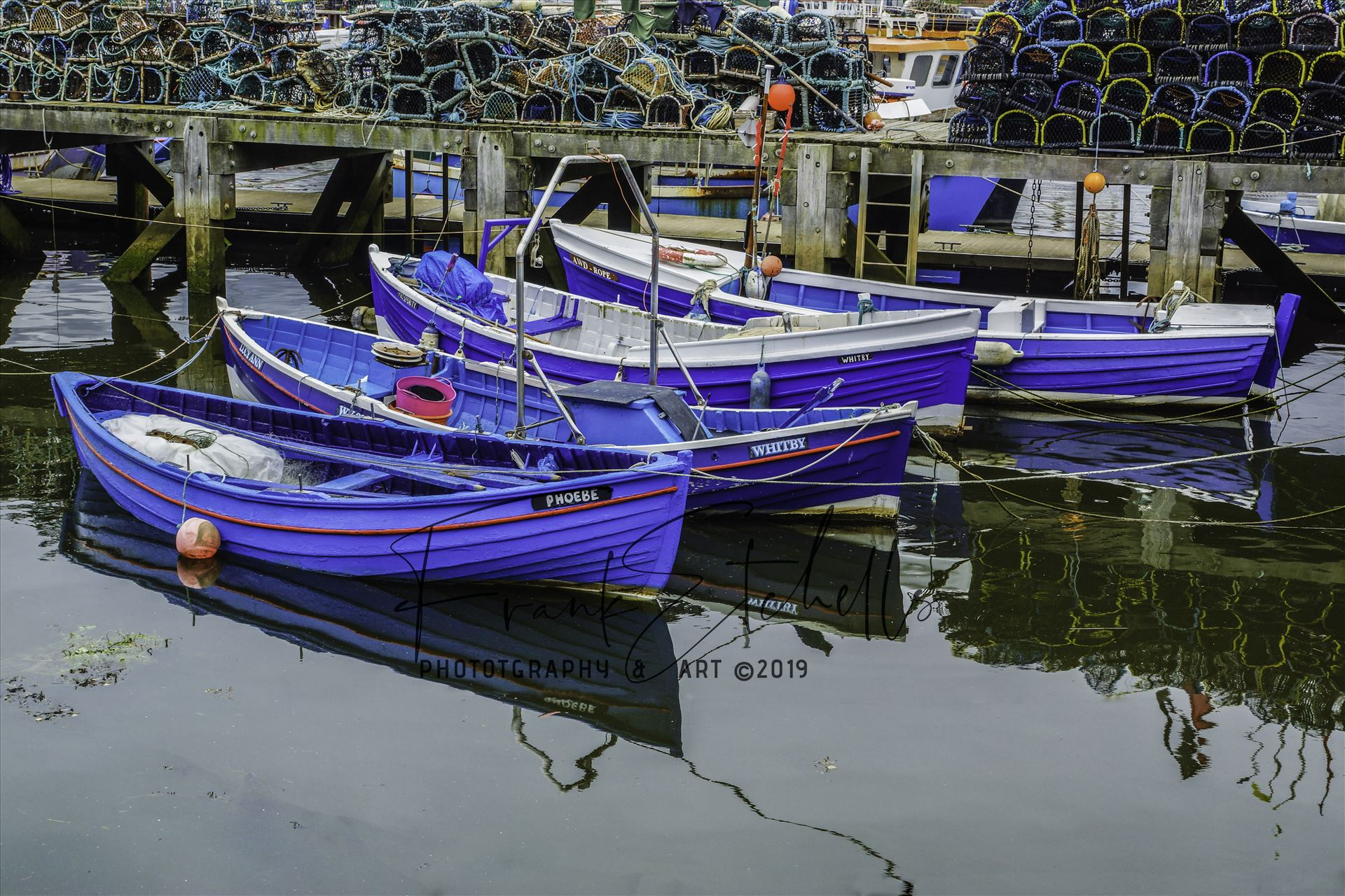 Four Tethered Boats - On a trip to Whitby in Yorkshire in 2012 and a walk through the town brought us to the harbour quay side and these tethered boats. So colourful and clean, nicely reflecting in the water of the River Esk and a large stack of lobster pots behind. by Frank Etchells Photography