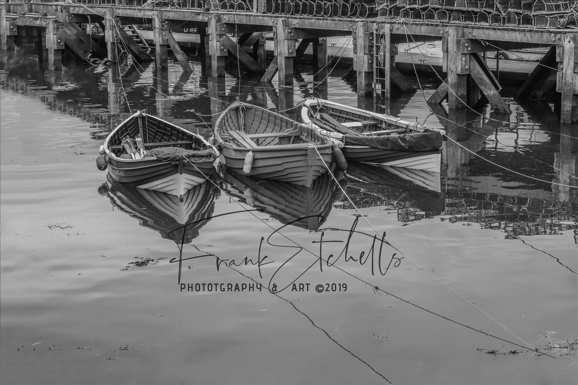 Tethered Boats Whitby 1, Edit; Duo-Tone - On a trip to Whitby in Yorkshire in 2012 and a walk through the town brought us to the harbour quay side and these small tethered boats, their bows and ropes reflected in the sea water and lobster pots neatly in stacks on the walkway. A