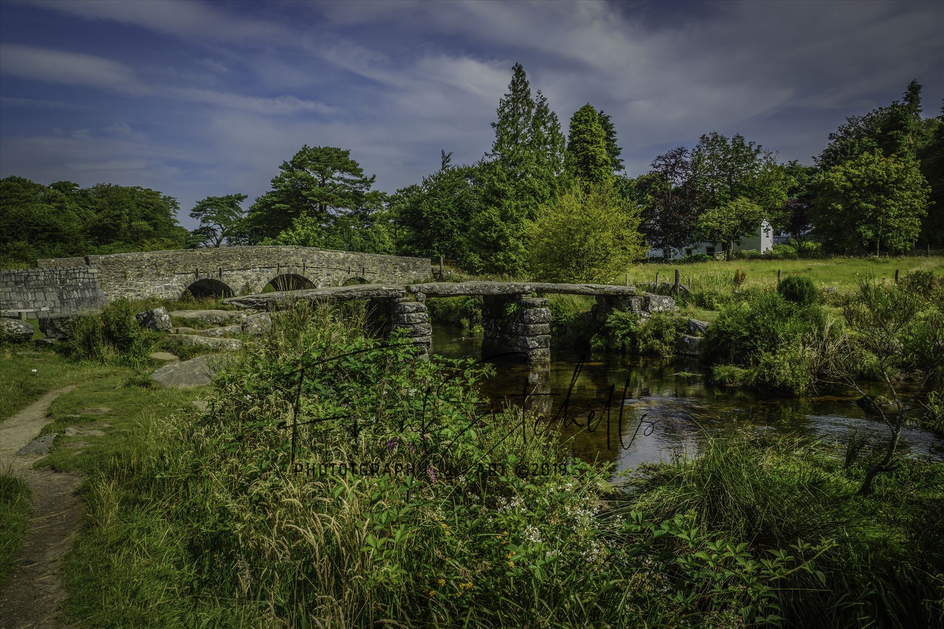 Postbridge Clapper Bridge 3 - A view of the 'Clapper Bridge' at Postbridge in the Dartmoor National Park on a warm August day visit while on the way to Cornwall with the main road bridge behind and a glimpse of the