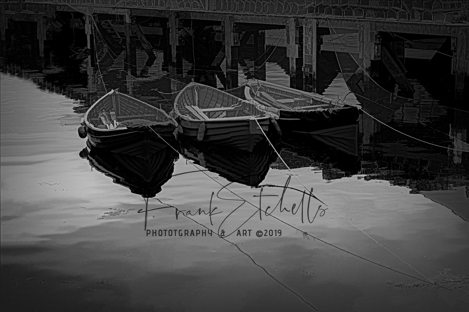 Tethered Boats, Whitby 1, Edit; Vector Subtle PA - On a trip to Whitby in Yorkshire in 2012 and a walk through the town brought us to the harbour quay side and these small tethered boats, their bows and ropes reflected in the sea water and lobster pots neatly in stacks on the walkway. A
