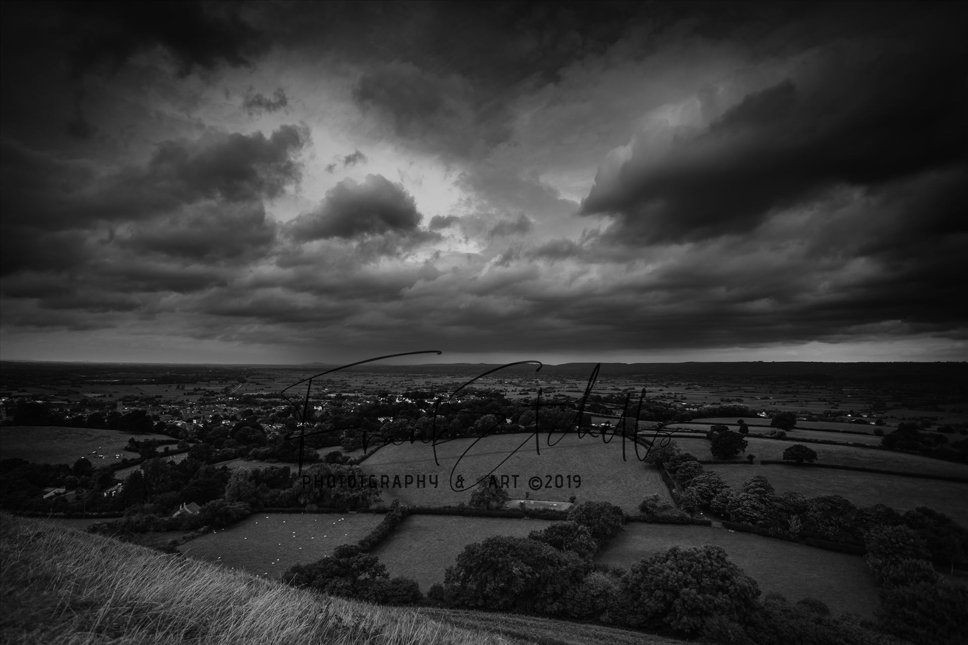 Approaching Storm Clouds BW - The wind blew strongly at the top and towards St. Michael's tower overlooking the surrounding lands bringing the clouds with it, they darkened and revealed approaching rain in the far distance... yet the sun broke briefly behind me to cast light below by Frank Etchells Photography
