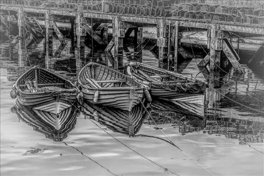 On a trip to Whitby in Yorkshire in 2012 and a walk through the town brought us to the harbour quay side and these small tethered boats, their bows and ropes reflected in the sea water and lobster pots neatly in stacks on the walkway. 'Cartoon' BWii edit.