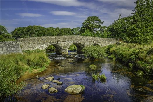 "A view of the bridge over the East Dart River at Postbridge, Dartmoor National Park from the ""Clapper Bridge"", on a summers August day visit."