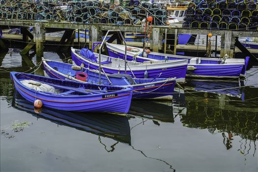On a trip to Whitby in Yorkshire in 2012 and a walk through the town brought us to the harbour quay side and these tethered boats. So colourful and clean, nicely reflecting in the water of the River Esk and a large stack of lobster pots behind.
