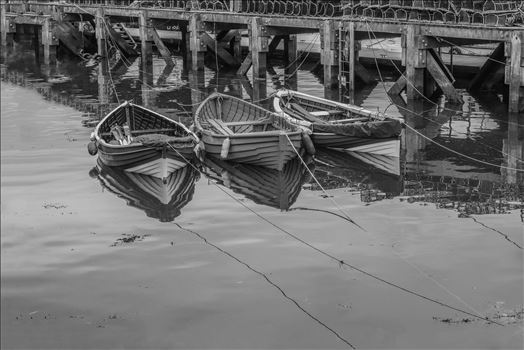 "On a trip to Whitby in Yorkshire in 2012 and a walk through the town brought us to the harbour quay side and these small tethered boats, their bows and ropes reflected in the sea water and lobster pots neatly in stacks on the walkway. A ""Duo-Tone"" Edit"