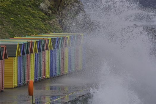 While on a visit in Whitby, Yorkshire, in 2012 - on a wild windy day I captured, in a number of shots taken, the high spray of the waves as they hit the wall of the walkway by the bright coloured huts... This was one shot without people in the scene