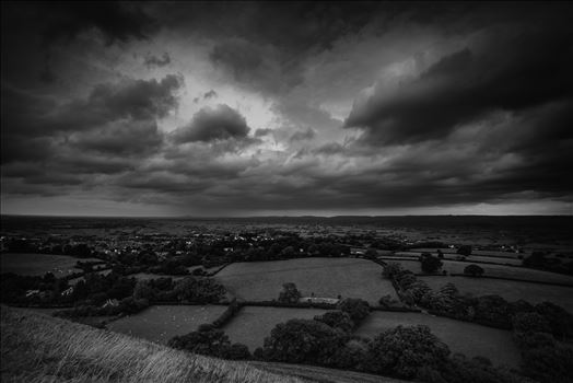 Approaching Storm Clouds BW - The wind blew strongly at the top and towards St. Michael's tower overlooking the surrounding lands bringing the clouds with it, they darkened and revealed approaching rain in the far distance... yet the sun broke briefly behind me to cast light below