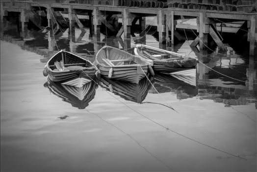 On a trip to Whitby in Yorkshire in 2012 and a walk through the town brought us to the harbour quay side and these small tethered boats, their bows and ropes reflected in the sea water and lobster pots neatly in stacks on the walkway. Line/Ink edit of the